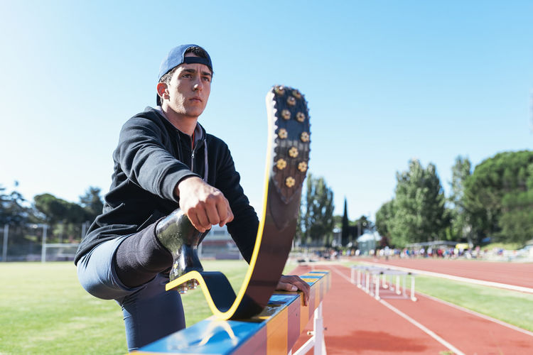 Young athlete stretching prosthetic leg on railing at running track