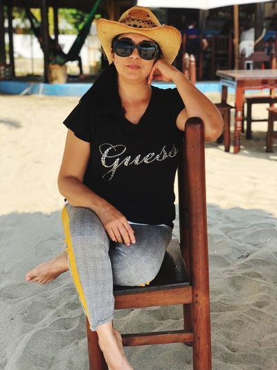 Portrait of woman in sunglasses and hat siting on chair at beach