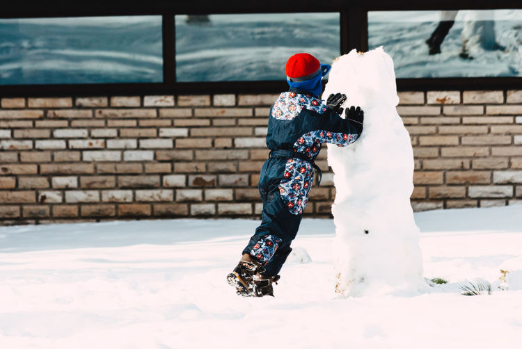Rear View Of Boy Playing With Snow In Yard During Winter