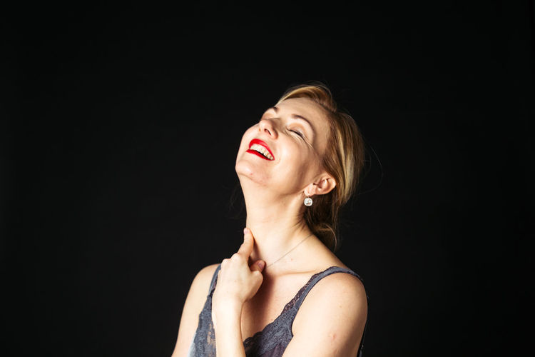 Smiling mature woman against black background