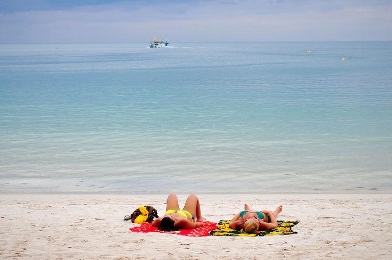 Two women sunbathing on the beautiful beach Woman Middle Age Women Friends Caucasian Sunbathing Sunbathe Summer Vacation Outdoor Activity Lesbian Couple Away Beautiful Beach White Sand Island Relaxing Relaxation Happiness Happy Seascape Leisure Lifestyle