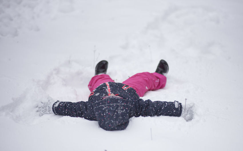 Close-up of girl lying on snow