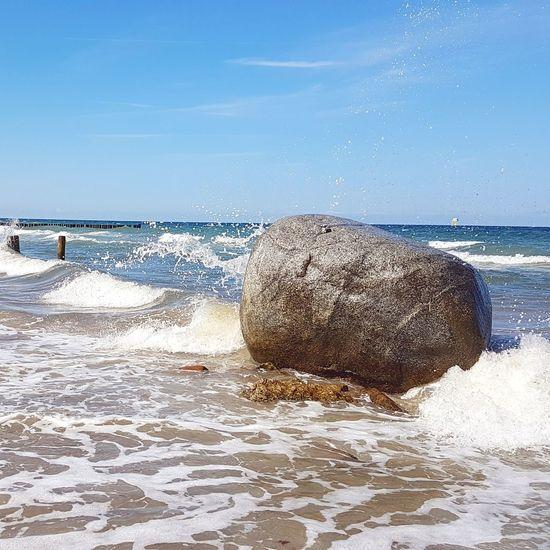 Sea waves splashing on rocks at shore against sky