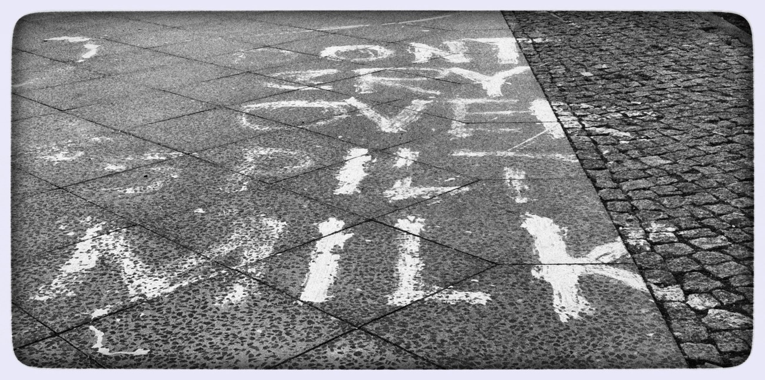 transfer print, auto post production filter, high angle view, street, text, road marking, communication, western script, shadow, guidance, cobblestone, road, day, outdoors, sunlight, asphalt, arrow symbol, directional sign, paving stone, sidewalk