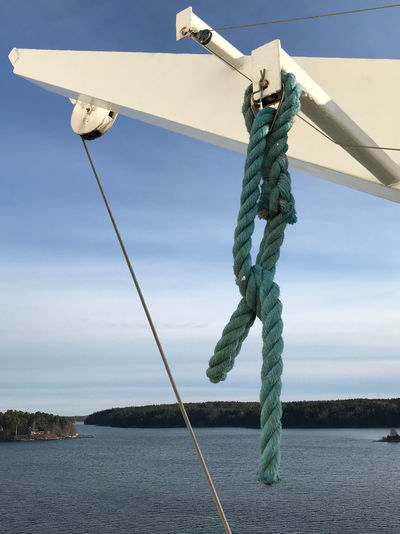 Low angle view of tied hanging on rope against sky