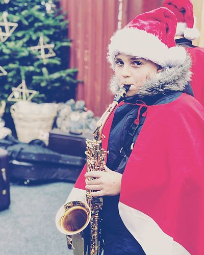 Portrait Of Girl Wearing Santa Hat Playing Saxophone