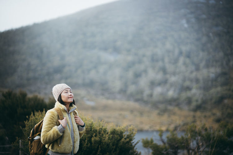 Smiling woman with eyes closed standing against mountain