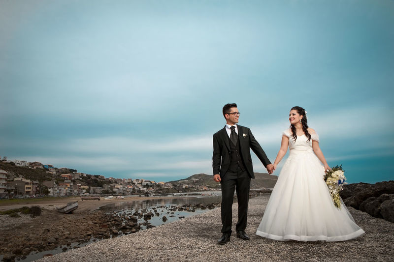 Wedding couple holding hands while standing against cloudy sky