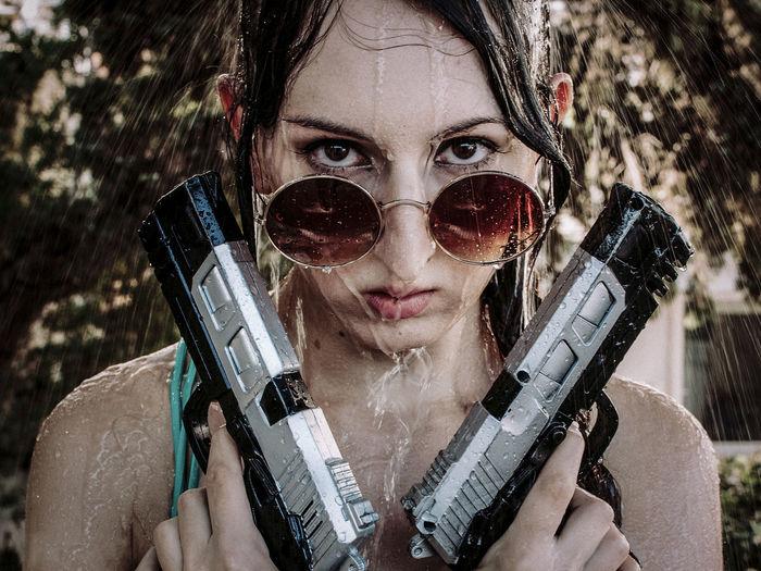 Portrait Of Woman Holding Guns Under Falling Water