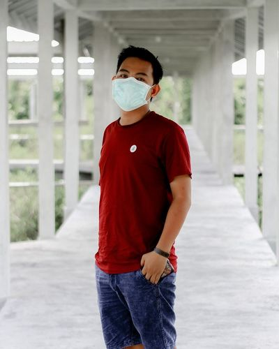 Portrait of young man wearing face mask standing on footbridge