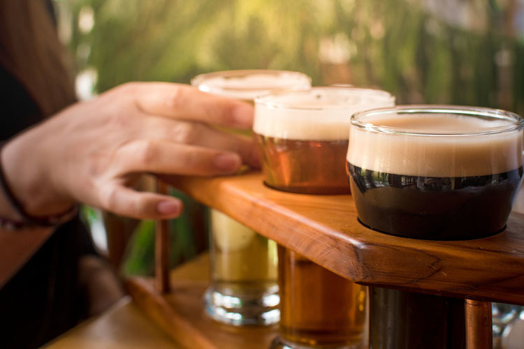 Cropped image of woman tasting craft beer at bar