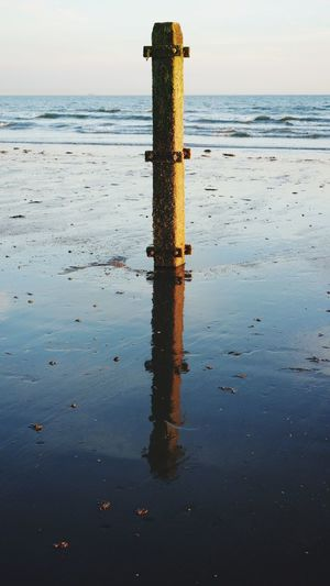 A wooden post secured in the sand complete with its own silhouette and reflection. Horizon Over Water Nature_collection EyeEm Best Shots Focus On Foreground Selective Focus Close-up Beauty In Nature Silhouette Sunlight Copy Space Clear Sky Wet Sand Wave Tidepools EyeEm Selects Water Sea Sky Horizon Over Water Beauty In Nature Wooden Post Beach Land Reflection Idyllic Day No People Outdoors Nature Scenics - Nature
