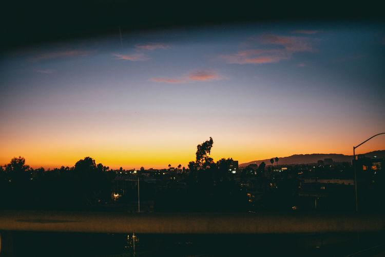 Illuminated city against sky during sunset