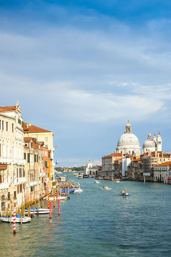 Grand canal by santa maria della salute in city against sky