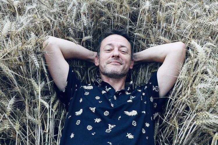 Portrait of man lying on field
