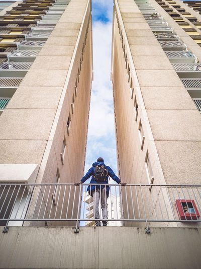 Low angle view of man standing by railing against buildings
