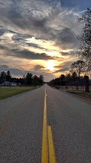 Surface level of empty road against sunset sky