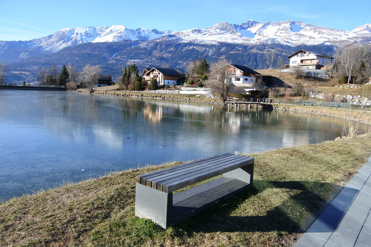mountain, mountain range, snow, cold temperature, water, day, tranquil scene, built structure, scenics, tranquility, nature, reflection, beauty in nature, winter, architecture, outdoors, building exterior, snowcapped mountain, sky, no people, lake, tree