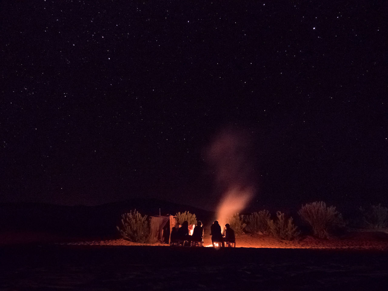 Silhouette People By Campfire Against Sky At Night