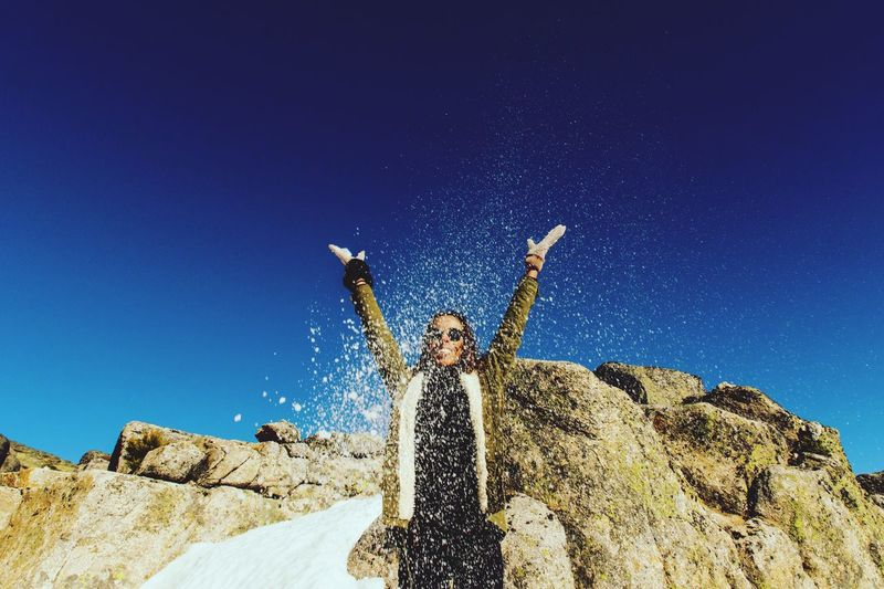 Playful woman throwing sand while standing against rock formations and clear blue sky