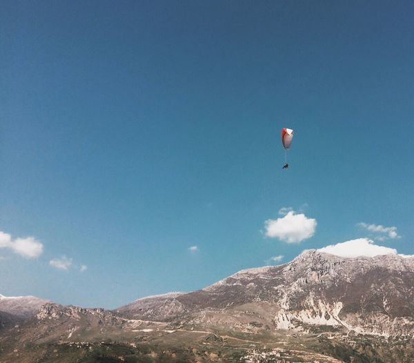 Low Angle View Of Person Paragliding Over Mountains Against Blue Sky