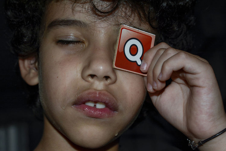 Close-up of boy crying while holding q sign