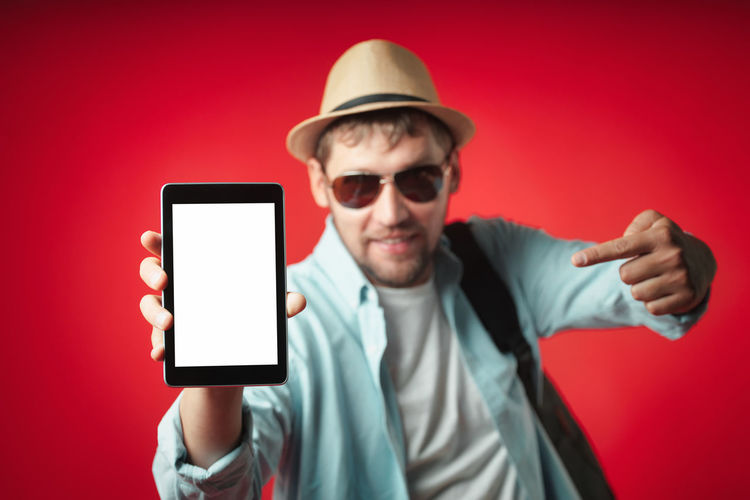 Portrait of young man using mobile phone against red background