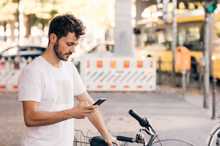 Young man looking at bicycle
