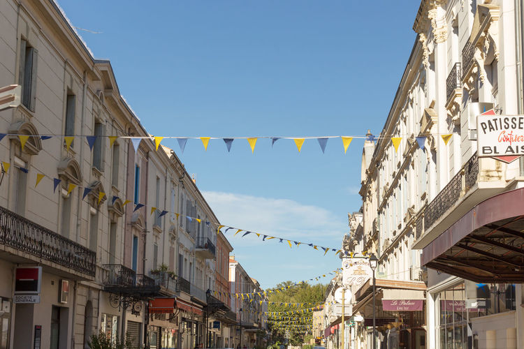 Decorated street in the Old town, Orange, France Architecture Building Exterior Built Structure Bunting City City Life Cloud Cloud - Sky Day Decoration Hanging Lantern Low Angle View Multi Colored No People Old Town Outdoors Residential Structure Sky