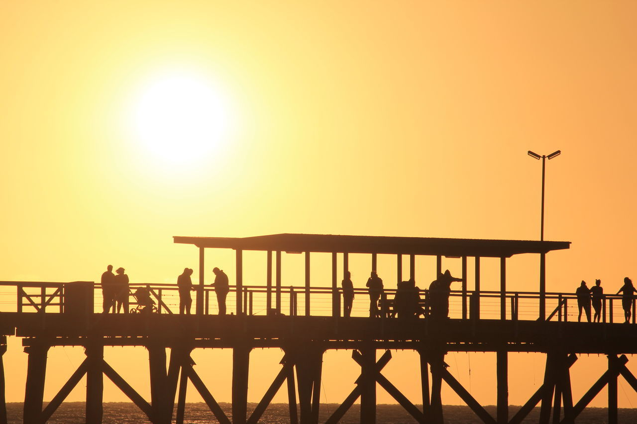 sky, sunset, real people, silhouette, group of people, men, lifestyles, railing, built structure, orange color, architecture, water, beauty in nature, nature, sun, sea, clear sky, pier, people, outdoors, bridge - man made structure
