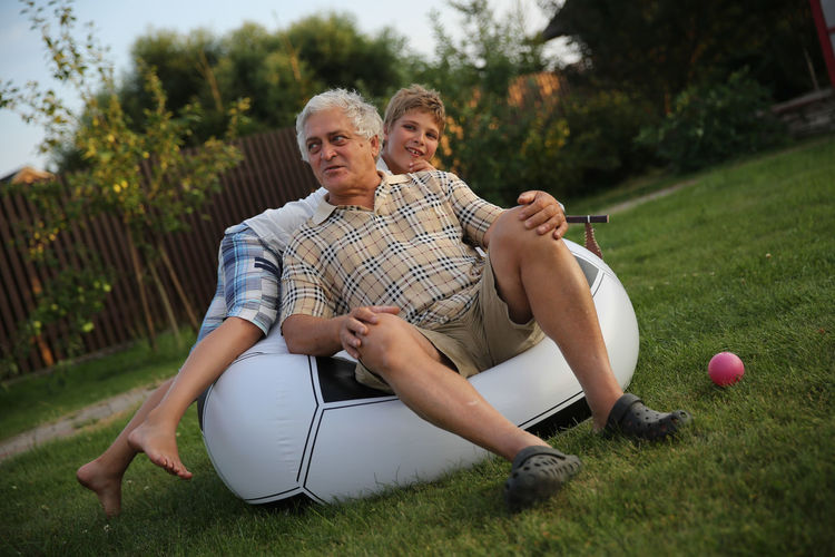 Tilt Shot Of Grandfather And Grandson On Bean Bag At Back Yard