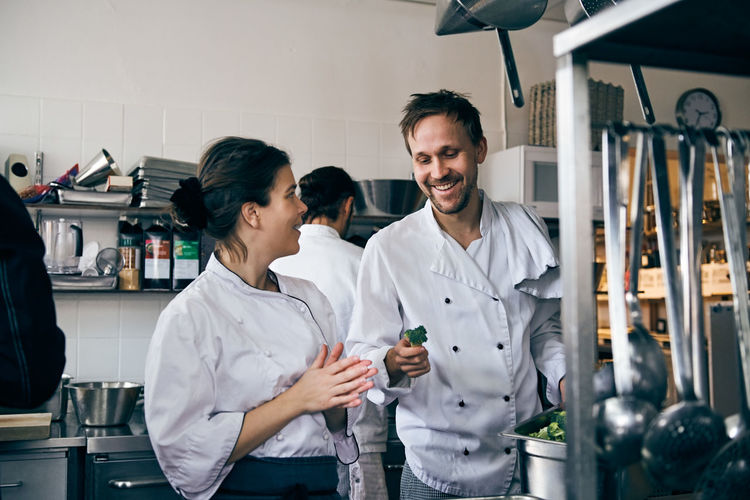 Male chef holding broccoli while talking with female colleague at kitchen