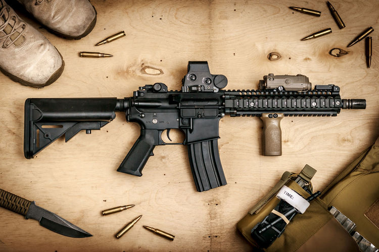 assault rifle on a wooden wall Knife Red Dot  Soldier Assault Assault Rifles Bullet Combat Day Gun Handgun Indoors  Laser Machinery Military No People Rifle Vest Weapon Weapons