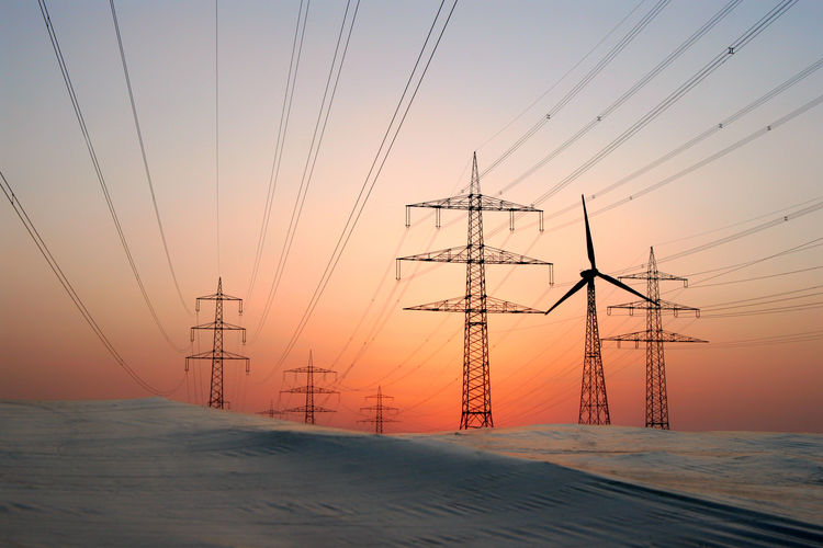 Electricity pylons on land against sky during sunset