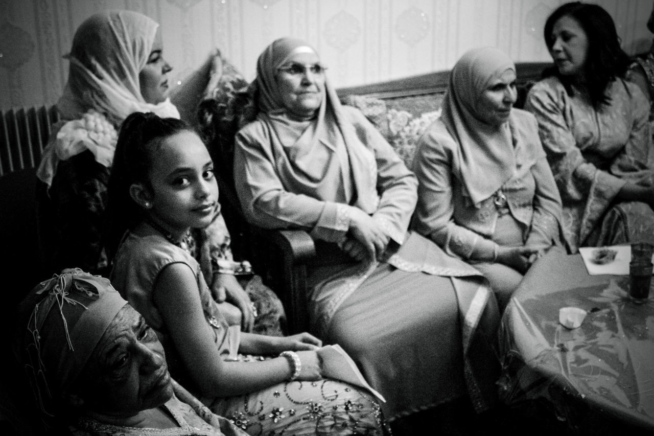 sitting, sofa, mother, indoors, looking at camera, family, girls, living room, togetherness, portrait, lifestyles, daughter, young women, domestic life, childhood, real people, group of people, young adult, women, bonding, night, adult, movie, people, film industry