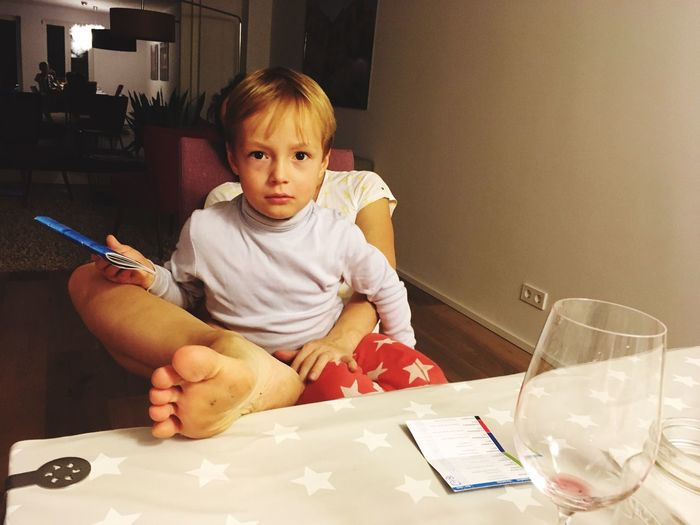 Portrait of cute boy sitting on table at home