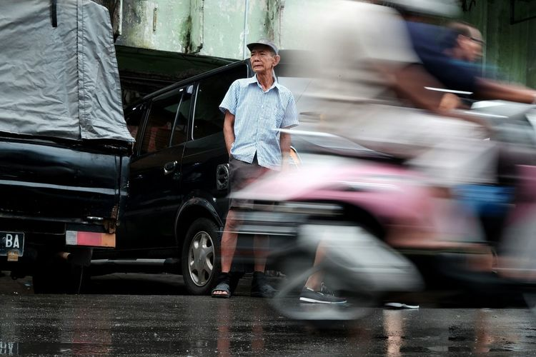 Man standing on road by car