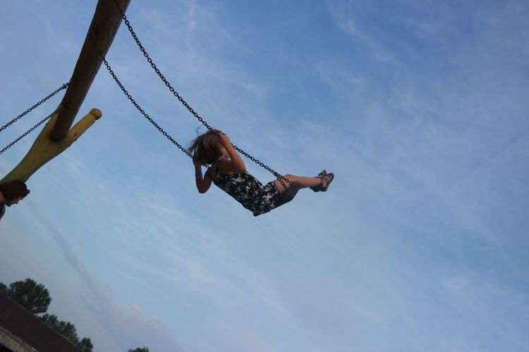 Low angle view of girl in swing against sky
