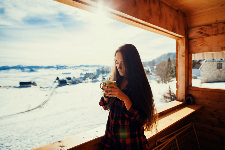 Girl drinks tea on winter terrace. Woman warming up drinking hot tea. Cold winter days in mountains. Coffee Cold Weather EyeEm Best Shots EyeEmNewHere Nature Tea Winter Wintertime Woman Cold Cold Days Cold Temperature Cold Winter ❄⛄ Day Drinking Female Hot Drink Long Hair Real People Snow Tea - Hot Drink Village Warming Up Winter Wonderland Women