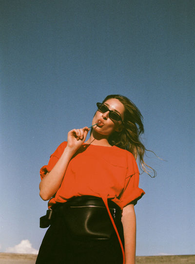 Low angle portrait of woman wearing sunglasses eating lollipop against clear sky