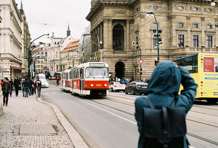 Rear View Of Man Standing Against Tram On City Street