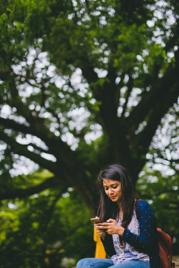 girl with the phone :P Casual Clothing Cute Day Focus On Foreground Gadget Girl Happiness Leisure Activity Lifestyles Long Hair Nature One Person Outdoors People Real People Sitting Smartphone Smiling Tree Young Adult Young Women