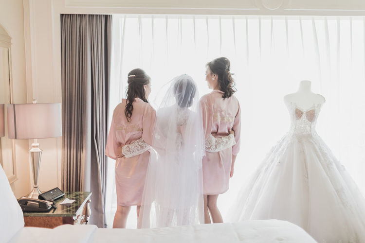 Bride with maids standing at home during wedding ceremony