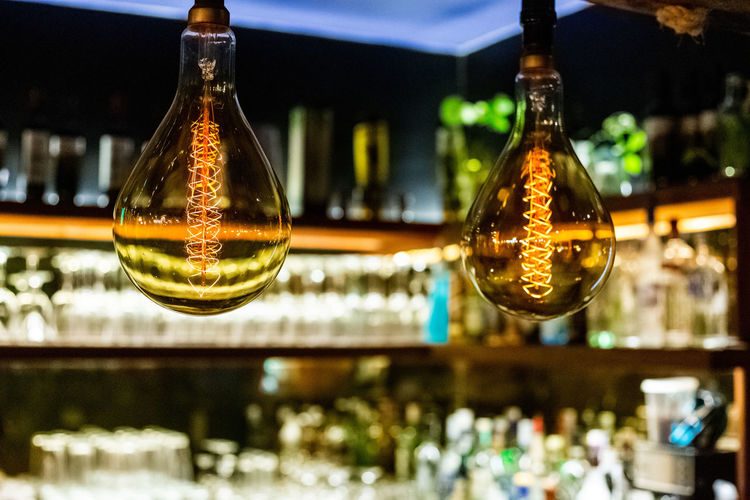 Focus On Foreground Glass - Material Bottle Illuminated Container Indoors  Close-up No People Bar - Drink Establishment Hanging Transparent Decoration Bar Counter Glass Food And Drink Still Life Reflection Restaurant Celebration Drink Nightlife