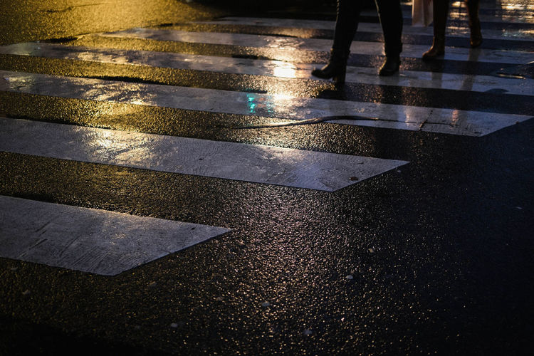 Nightphotography City Crossing Crosswalk Human Leg Low Section Marking Outdoors Rain Rainy Season Road Sign Street Transportation Walking Water Wet Zebra Crossing