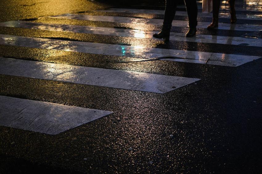 Nightphotography City Crossing Crosswalk Human Leg Low Section Marking Outdoors Rain Rainy Season Road Sign Street Transportation Walking Water Wet Zebra Crossing
