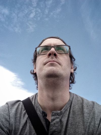 Low angle view of thoughtful mid adult man against blue sky