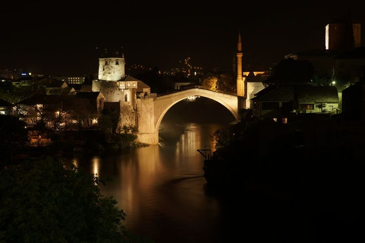 Arch bridge over river against buildings at night