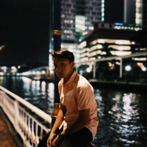 Young man sitting on railing by river in city at night