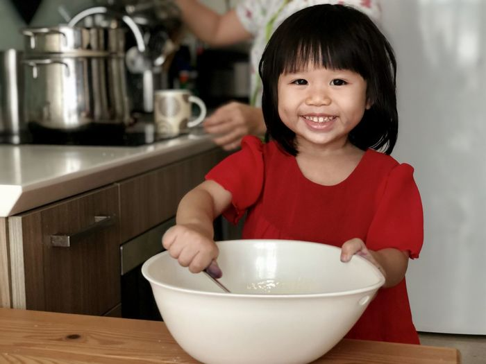 Portrait of cute girl in bowl at home